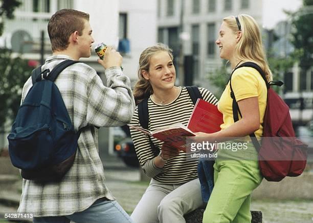 Zwei Mädchen und ein Junge treffen sich lachend auf der Straße Die Jugendlichen tragen Rucksäcke auf ihren Rücken Der Junge trinkt aus einer Dose die...