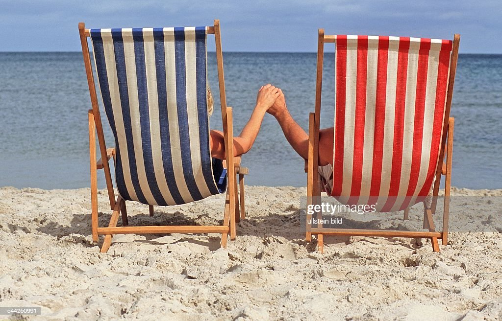 zwei menschen liegen im liegestuhl am strand news photo getty images. Black Bedroom Furniture Sets. Home Design Ideas