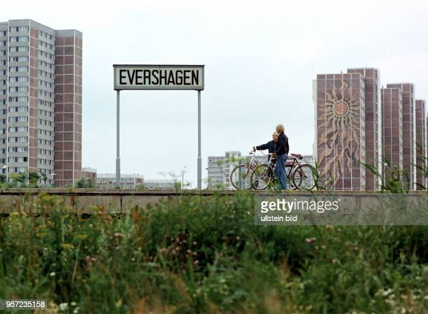 Zwei Männer unterhalten sich auf dem Bahnsteig der SBahnstation Evershagen in Rostock im Hintergrund die Neubauten von RostockEvershagen mit einem...