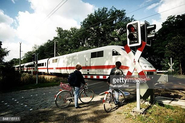 zwei Radfahrer warten an einem Bahnübergang mit Schranke bis ein ICE vorüber fährt 1997