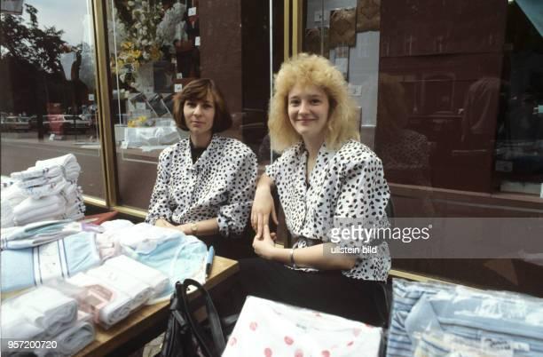 Zwei Verkäuferinnen bieten in der Brunnenstraße in BerlinOst TextilProdukte auf dem Gehweg vor dem Geschäft an undatiertes Foto von 1990 Mit der...