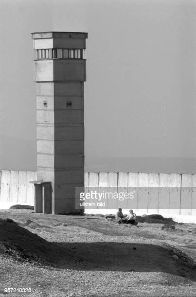 Zwei Wanderer machen vor der Mauer und einem Wachturm auf dem Brocken eine Rast aufgenommen imMärz 1990 Der Brocken im Harz war bis zur deutschen...