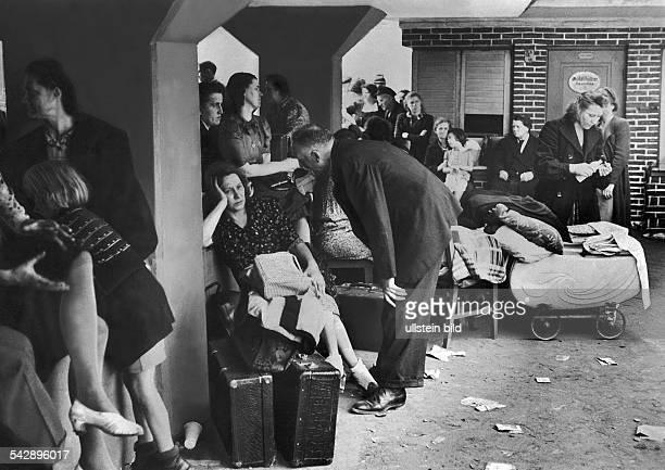 Menschen im Eingangsbereich des Bunkers an der Reeperbahn Meist Frauen und Kinder sitzen auf den wenigen Habseligkeiten Koffer Taschen und Stühlen...