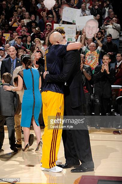 Zydrunas Ilgauskas hugs Anderson Varejao of the Cleveland Cavaliers during halftime of the game against the New York Knicks at The Quicken Loans...