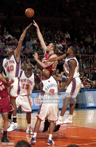 Zydrunas Ilgauskas of the Cleveland Cavaliers attempts jumpshot over Kurt Thomas Nazr Mohammed Stephon Marbury and Trevor Ariza of the New York...