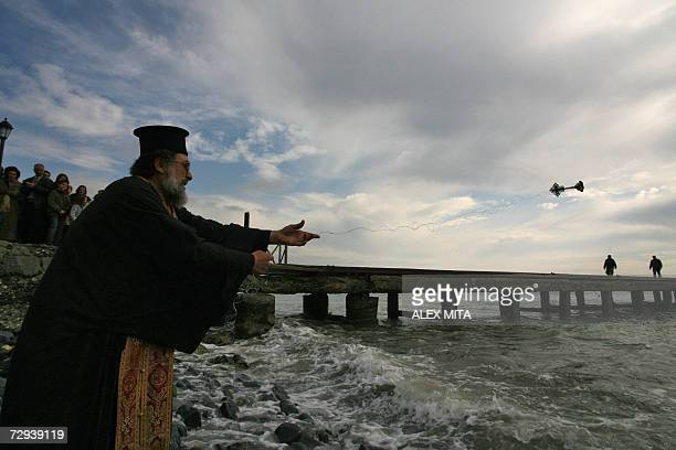 A Greek Orthodox priest throws a cross into the sea in a religious ceremony to blesss the waters in the coastal town of Zygi 06 January 2007 to mark...