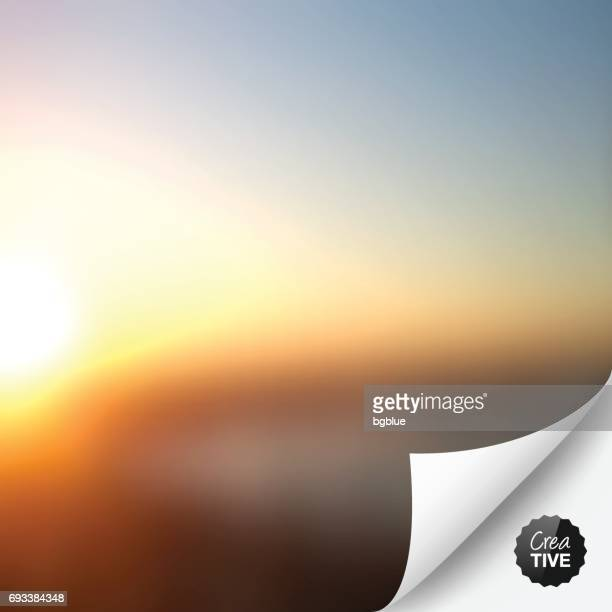 Abstract background, blurred sunset with curled page