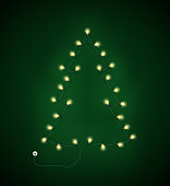 Abstract Christmas tree made from lighting garland on green backgroun