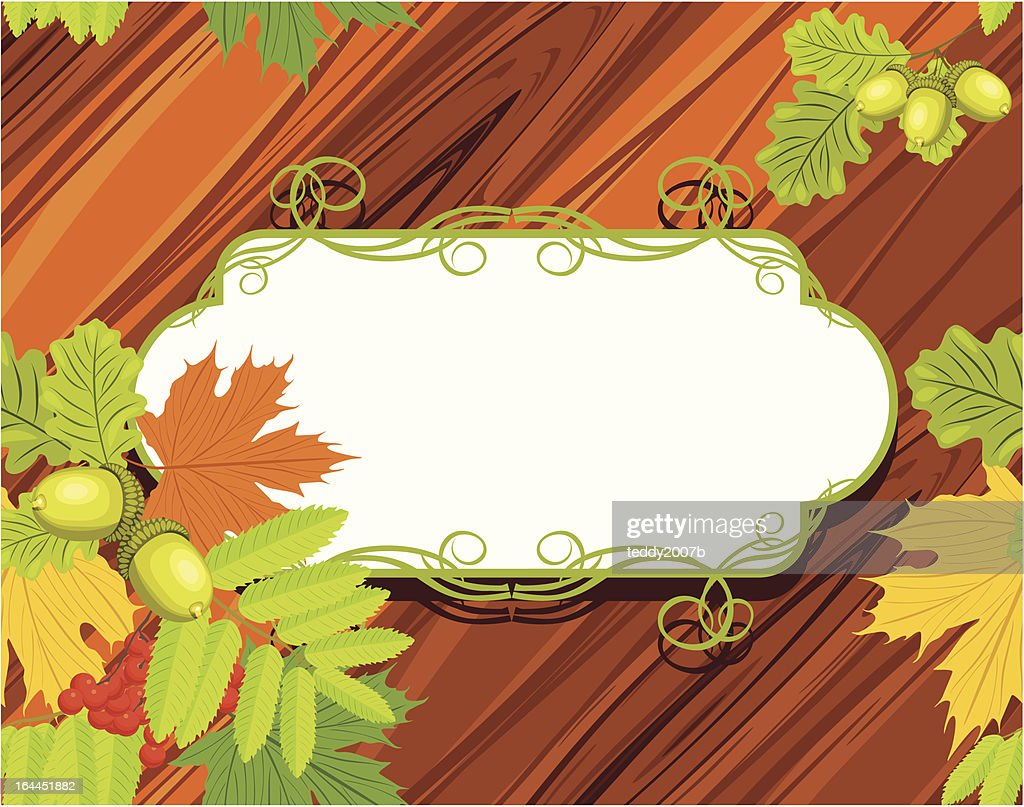 Acorns, rowan and maple leaves on the wooden background