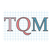 TQM (Total Quality Management) acronym on checkered paper sheet