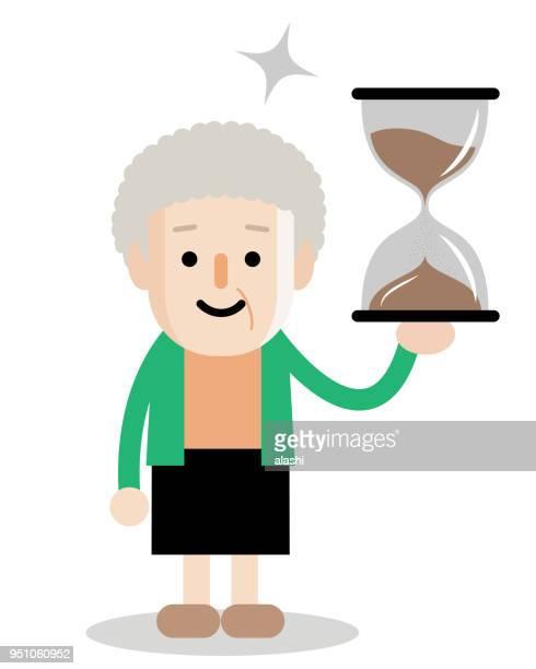 砂時計の砂の時計の年配の女性をアクティブと健康的なライフ スタイル