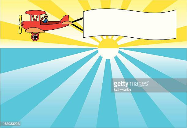 advertising biplane at sunset - biplane stock illustrations, clip art, cartoons, & icons