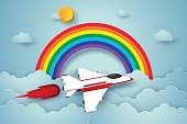 Airplane flying on blue sky with rainbow