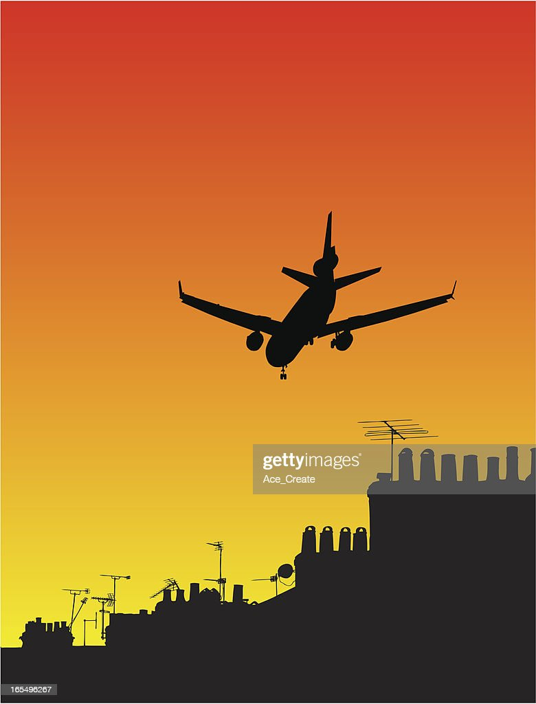 Airplane silhouette at sunset over rooftops