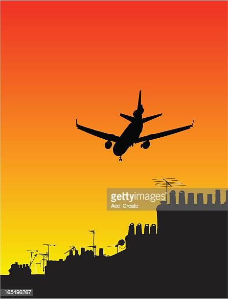 Silhueta de avião ao pôr do sol sobre os telhados