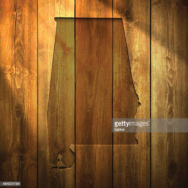 alabama map on lit wooden background - alabama stock illustrations, clip art, cartoons, & icons
