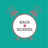 Alarm clock with chalk text green background Back to school