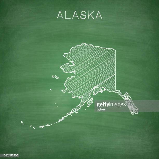 alaska map drawn on chalkboard - blackboard - alaska us state stock illustrations