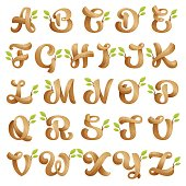 Alphabet icons with wood texture and green leaves.