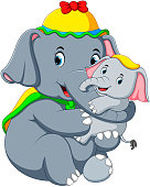 an elephant wearing a yellow hat and playing with a little elephant so fun