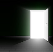 An open door in a dark room. A ray of light shines into the darkness. A bright way out.