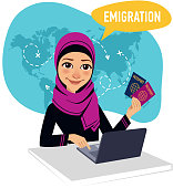 Arab woman sitting at table in office and working for laptop. Woman draws up documents for emigration.