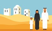 Arabic Family in traditional clothes in desert dunes