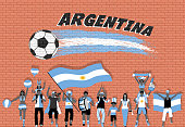 Argentinian football fans cheering with Argentina flag colors in front of soccer ball graffiti