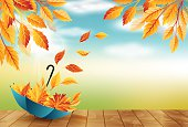Autumn background with umbrella, flying fall leaves and blue sky