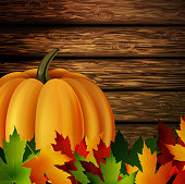 Autumn leaves and pumpkin on wooden texture