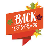 Back to school lettering on orange ribbon banner with autumn leaves around.
