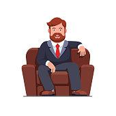 Bearded business man sitting on big arm chair