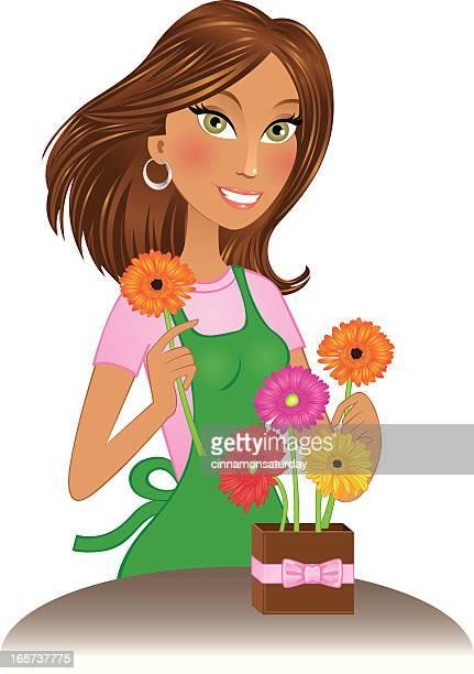 Beautiful brunette florist arranging gerbera daisies