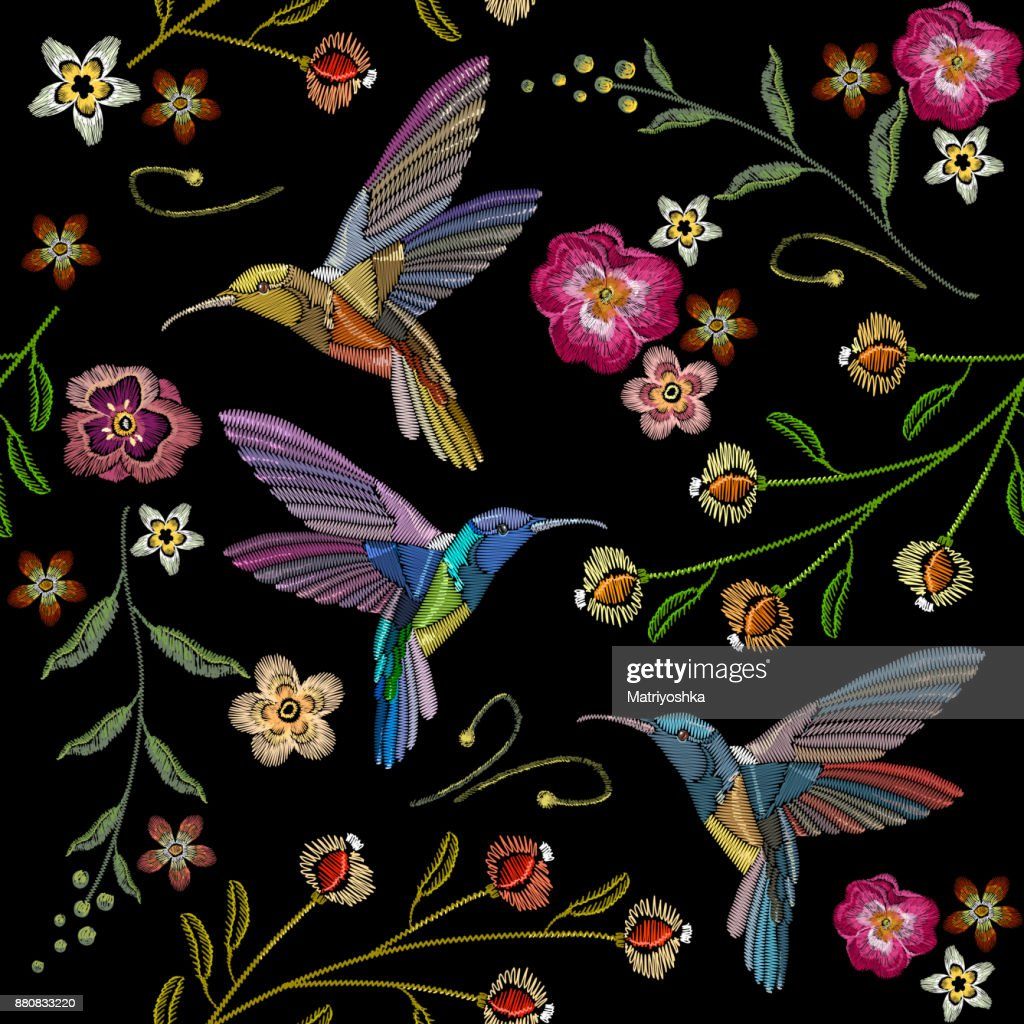 Beautiful hummingbirds and exotic flowers embroidery on black background. Template for clothes, textiles, t-shirt design. Humming bird and tropical flowers embroidery seamless pattern