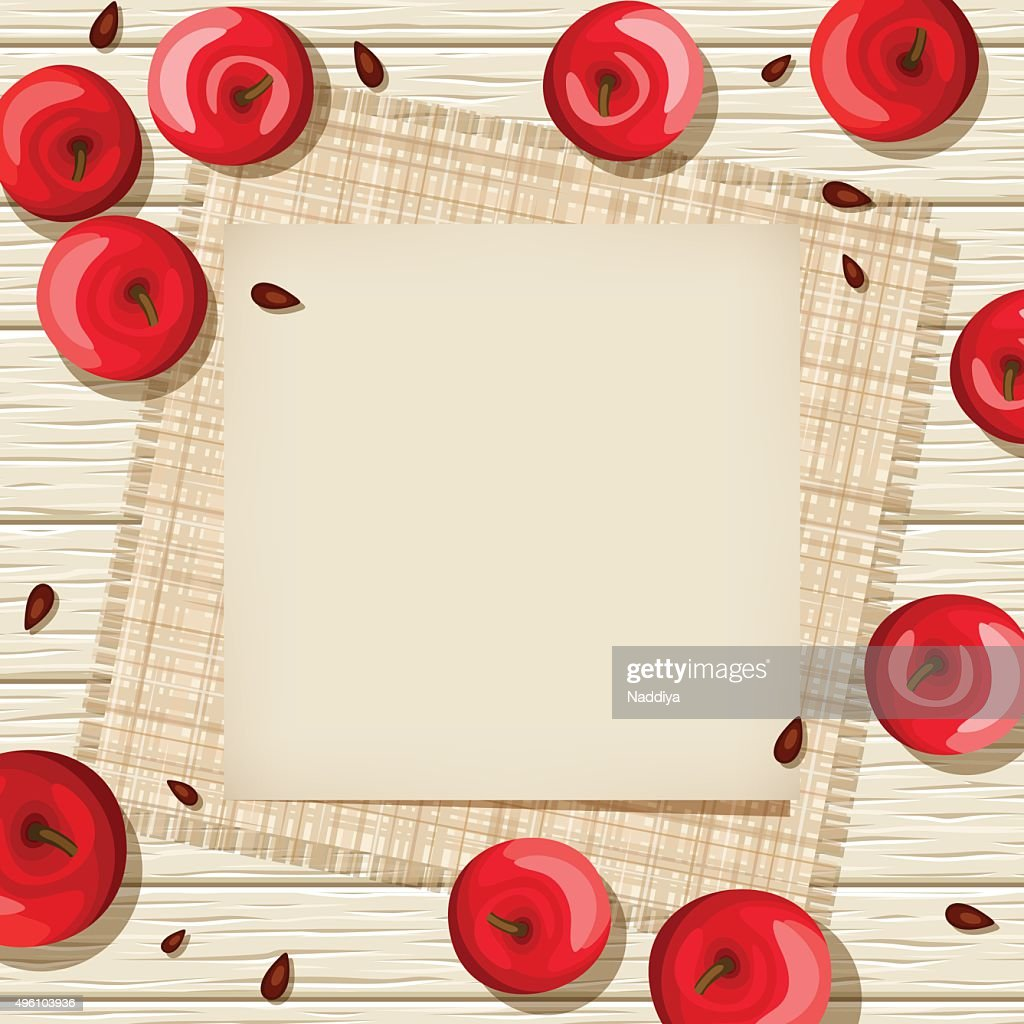 Beige card on wooden background with red apples and sacking.