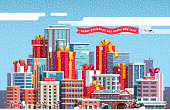 Big city skyline with huge skyscraper sized New Year and Merry Christmas themed gift boxes with ribbon bows. Snow falling over town and presents. Flat isolated vector