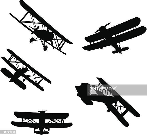 biplane silhouetes - biplane stock illustrations, clip art, cartoons, & icons