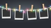 Blank photo frame hanging on rope with colorful fairy lights