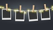 Blank photo frame hanging on rope with fairy lights