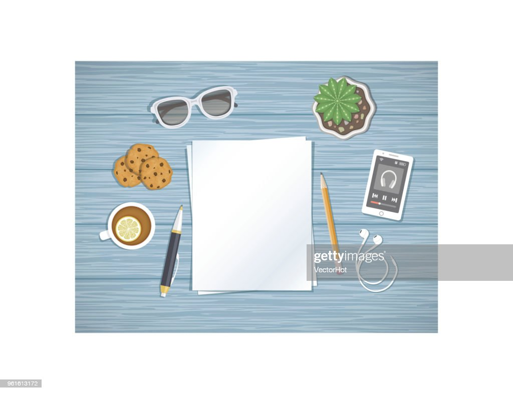 Blank sheets of paper on the desktop. Top view of paper, pen, pencil, smartphone running the music player, headphones, sunglasses, tea with lemon,cookies.