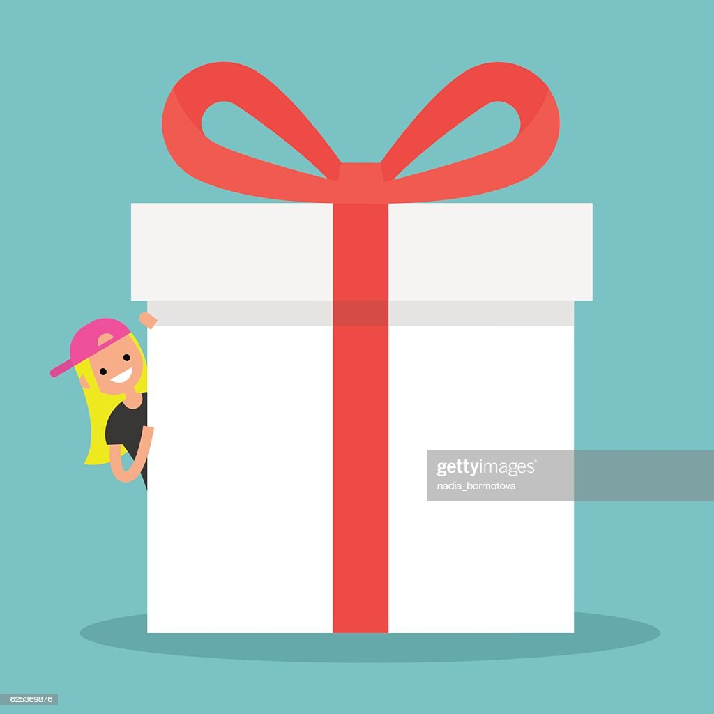 Blond girl peeping from behind a giant gift box
