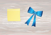 Blue bow . Vector on wooden background. For a holiday or a party. Yellow sheet of paper for notes. Sticker.
