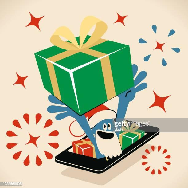 サンタの帽子とひげの頭の上の巨大なギフト ボックスを運ぶ携帯電話からブルーマン - クリスマスマーケット点のイラスト素材/クリップアート素材/マンガ素材/アイコン素材
