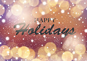 Blurred light gold bokeh abstract background with happy holidays lettering