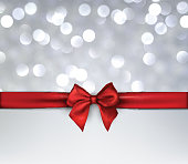 Bokeh holiday background with red bow.