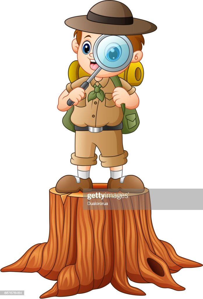 Boy explorer with magnifying glass on tree stump