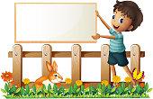 boy holding a framed board in the garden