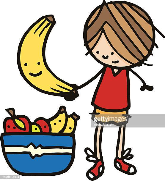 Boy holding a large banana next to bowl of fruit