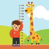 Boy kid measuring his height at kindergarten wall