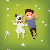 Boy lies with the dog on the lawn. Vector illustration